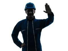 man construction worker saluting silhouette portrait - stock photo