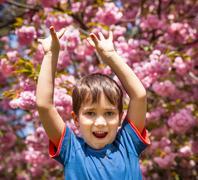 boy with hands up against cherry blossoms background - stock photo
