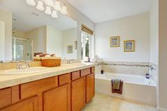 bathroom with honey tone vanity cabinet - stock photo