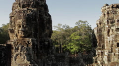 Large head carvings on pillars that form the detailed architecture of the Bayon  Stock Footage