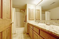 bathroom interior with in soft ivory tones with wooden cabinet - stock photo