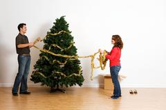 Christmas: putting tinsel or garland on tree Stock Photos
