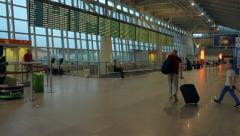 People with suitcases wait for departure in the Warsaw Chopin Airport Stock Footage