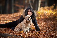 girl and cocker spaniel in the autumn forest - stock photo