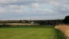 A small plane landing on a green field Stock Footage