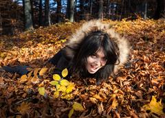 Girl and fallen autumn leaves Stock Photos