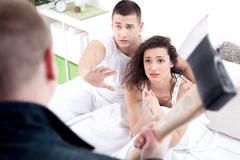 caught in cheating, angry husband holding the hatchet, a woman and a man beg  - stock photo
