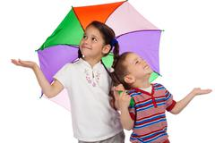 Little children with umbrella, checking for rain Stock Photos