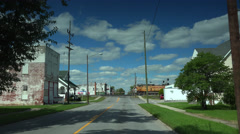 Driving toward a train crossing in small town Stock Footage