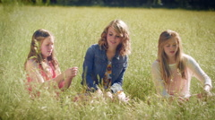 3 Girls Sit In A Meadow And Pick Grass To Make Crowns For Their Hair - stock footage