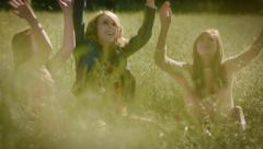 3 Sisters Sit In A Field, They Playfully Throw Grass In The Air Stock Footage