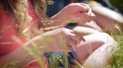 Closeup Of Girl's Hands Making Grass Crown, Closeup Of Her Face (Concentrating) - stock footage