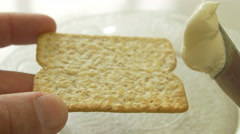 Spreading cheese on a whole wheat cracker 4K Stock Footage