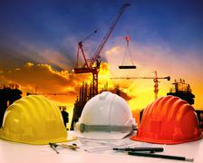 Safety helmet on civil engineer working table against crane lifting meterial  Stock Photos