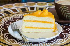 Orange cake and late  cofee cup on a table Stock Photos