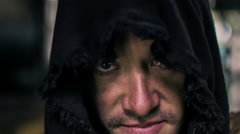 A hooded man looks up and flashes an evil smile Stock Footage