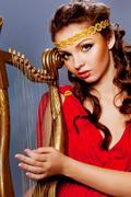 beautiful young girl playing the harp - stock photo