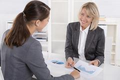 Two business woman sitting at desk: customer and adviser talking together. Stock Photos