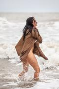 seminude woman in the cold sea waves - stock photo