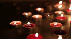 Slow camera move over moody red candles  - stock footage