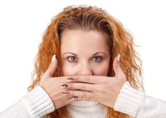 woman covering her mouth by the hand - stock photo