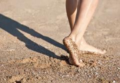 legs on the sand beach - stock photo