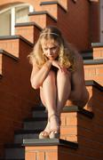 young beautiful naked woman sunbathing on the stairs - stock photo