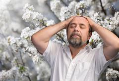 man enjoying nature in the flowered garden - stock photo