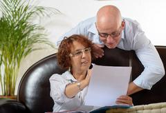 senior couple looks at a document - stock photo