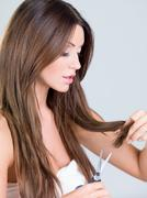 Pretty Woman Trimming Her Hair Using Scissors Stock Photos