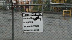 CCTV sign on factory fence. - stock footage