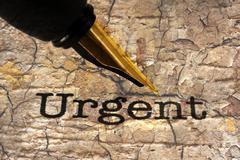 Fountain pen on urgent text Stock Photos