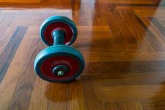 Dumbells on wooden floor Stock Photos