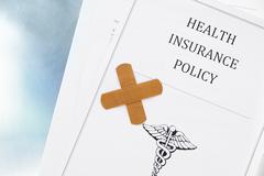 health insurance policy with bandage, shot from above - stock photo