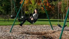 Beautiful Young Woman Swinging on Swing in Autumn Setting Stock Footage