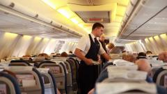 Stewards serve passengers on the plane. Stock Footage