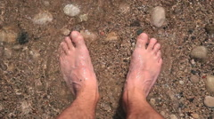 Close-up of male feet on the beach. The waves and sand. Stock Footage
