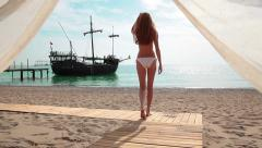 Beautiful girl with red hair comes out of the Bungalow towards the sea. Stock Footage