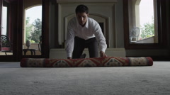 Medium shot of man unrolling rug in living room / Cedar Hills, Utah, United Stock Footage