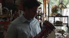 Medium shot of man looking at bongo drum in antique shop / Provo, Utah, United Stock Footage