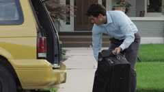 Medium panning shot of businessman loading suitcase into hatchback of minivan Stock Footage
