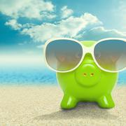 Piggy bank in sunglasses on the beach - vacation concept Stock Photos