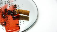 quit smoking. cigarette butt and ash in blood on a dish - stock photo