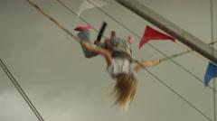 Medium panning shot of girl on bungee trampoline at amusement park / Salt Lake Stock Footage