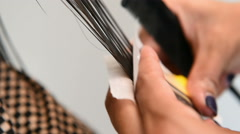 Hands of a female hairstylist doing a perm rolling the clients hair Stock Footage