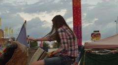 Time lapse medium shot of teenage girl riding mechanical bull at amusement park Stock Footage
