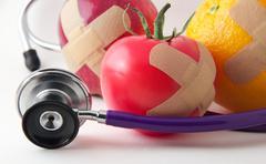bandaged apple tomato and orange with stethescope to promote good health - stock photo