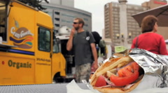 Time lapse of people walking by food truck trucks with pita sandwich on table - stock footage