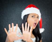 Closeup portrait of scared helper woman with red santa claus hat, raising han Stock Photos