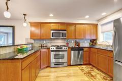 maple kitchen cabinets with steel appliances and granite tops - stock photo